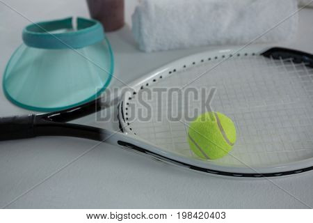 High angle view of tennis ball on racket by sun visor against white background