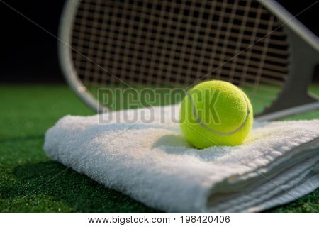Close up of tennis ball on napkin by racket at playing field