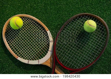 Overhead view of tennis balls on rackets at playing field