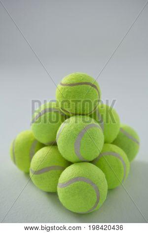 Heap of fluorescent yellow tennis balls on white background