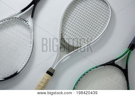 High angle view of metallic tennis rackets on white background