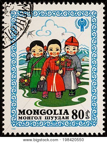 Moscow Russia - August 05 2017: A stamp printed in Mongolia shows children in Mongolian national costumes with bouquets of flowers go to school series
