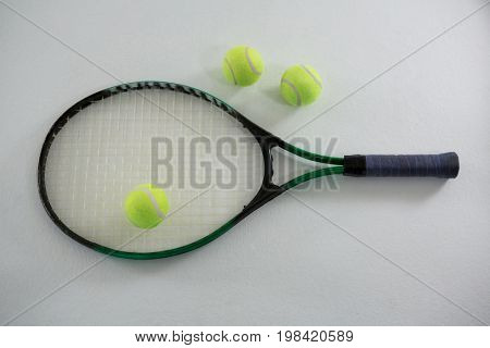 Overhead view of tennis balls with racket on white background