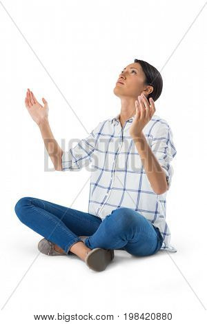 Thoughtful woman praying against white background