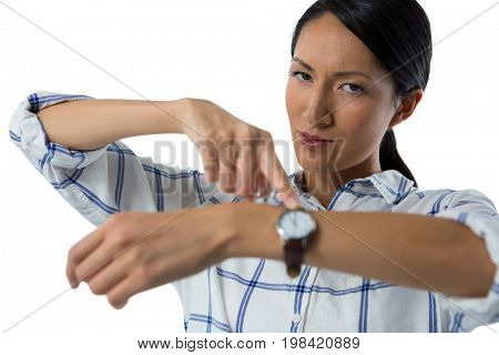 Female executive pointing at her wristwatch against white background