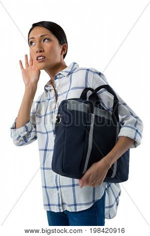 Close-up of female executive with briefcase listening secretly with hands behind her ears