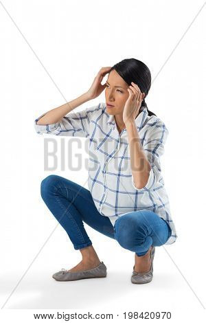 Sad woman crouching against white background