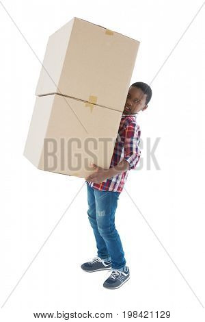 Portrait of boy carrying heavy boxes against white background