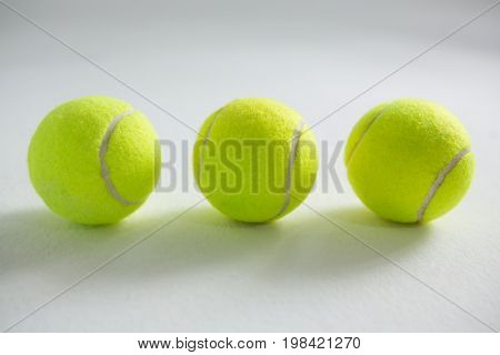 High angle view of fluorescent tennis balls on white background