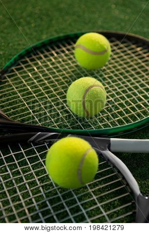 Close up of tennis balls on rackets at field