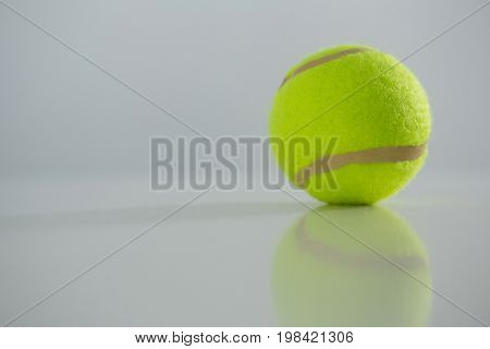 Close up of fluorescent tennis ball against white background