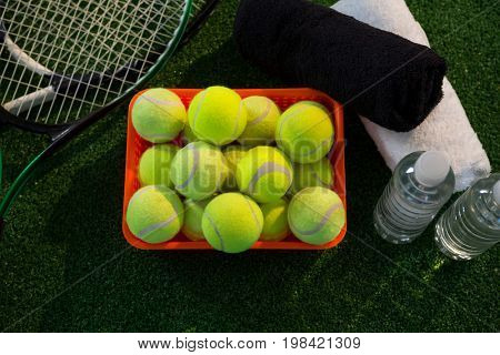 Overhead view of tennis balls in container amidst rackets and napkins by water bottles on field