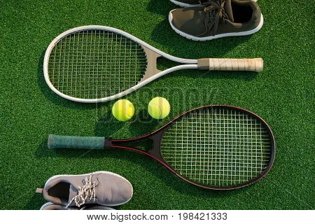Overhead view of tennis rackets with balls and sports shoes on field