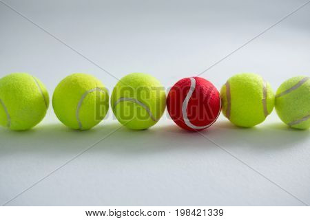 Tennis balls arranged side by side against white background
