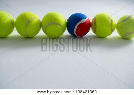 Tennis balls arranged side by side on white background