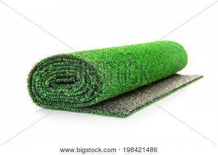Roll of artificial grass mat on white background