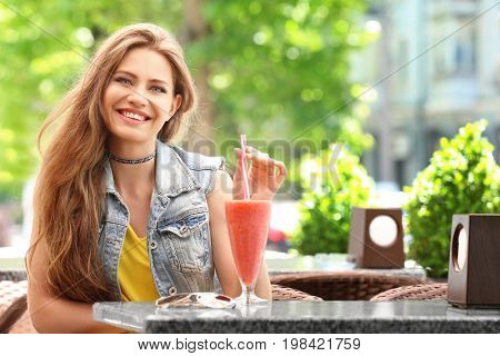 Pretty woman drinking tasty smoothie in cafe