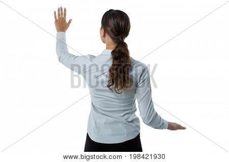 Rear view of female executive pretending to touch an invisible screen against white background