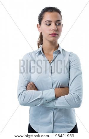 Thoughtful female executive standing with arms crossed against white background