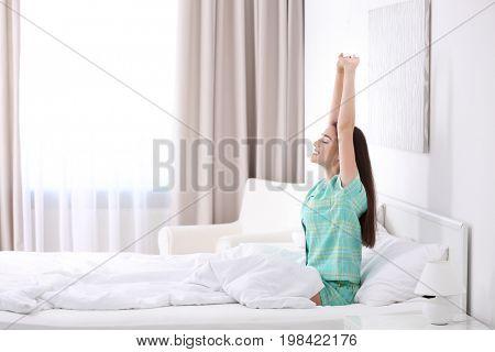 Young beautiful woman awaking in light hotel room