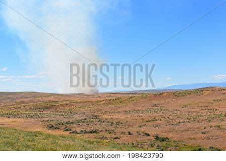 Prairie Fire in Wyoming. Smoke rises from a small brush fire.