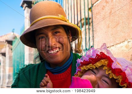 Andean indigenous woman and daughter in traditional inca customs in Cusco, Peru