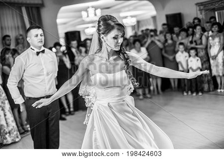 Beautiful caucasian couple just married and dancing their first dance confetti and heavy smoke around. Bride and groom kiss.