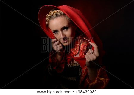 beautiful woman with red cloak posing in studio