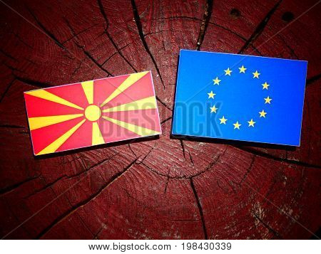 Macedonian Flag With Eu Flag On A Tree Stump Isolated