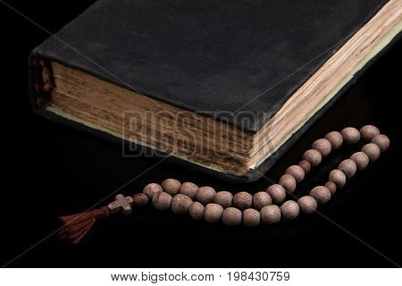 Sacred book and rosary on a black background