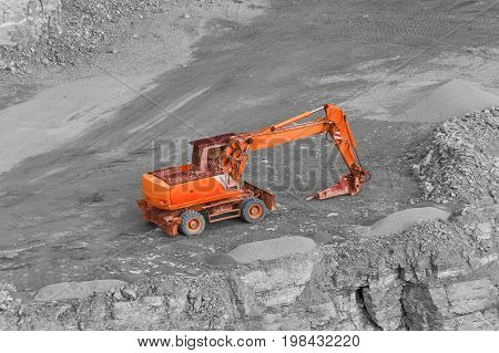 tracked red excavator in rocky quarry ambiance