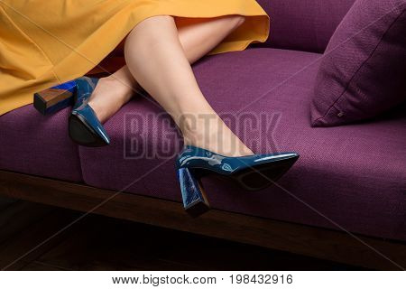 A young girl in a yellow skirt and blue shoes lies on a sofa in the studio