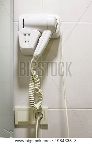 A modern electric hairdryer on the hotel wall. closeup