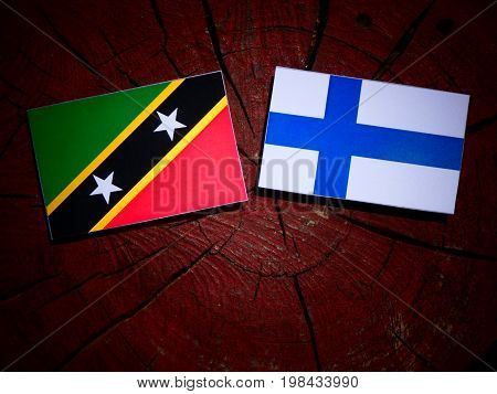 Saint Kitts And Nevis Flag With Finnish Flag On A Tree Stump Isolated