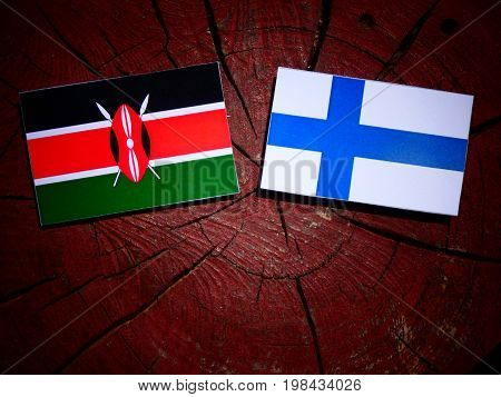 Kenyan Flag With Finnish Flag On A Tree Stump Isolated