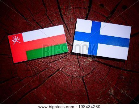 Omani Flag With Finnish Flag On A Tree Stump Isolated