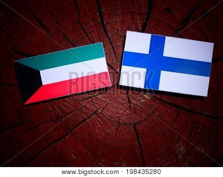 Kuwaiti Flag With Finnish Flag On A Tree Stump Isolated
