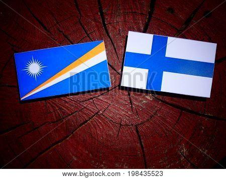 Marshall Islands Flag With Finnish Flag On A Tree Stump Isolated