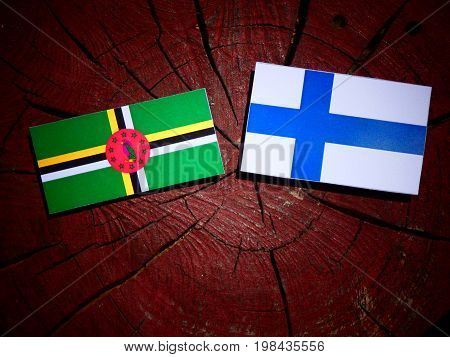 Dominica Flag With Finnish Flag On A Tree Stump Isolated