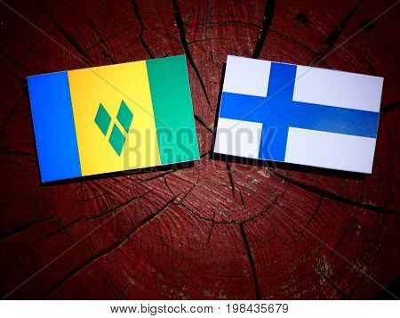 Saint Vincent And The Grenadines Flag With Finnish Flag On A Tree Stump Isolated