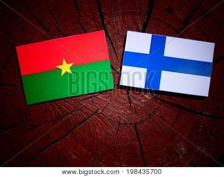 Burkina Faso Flag With Finnish Flag On A Tree Stump Isolated