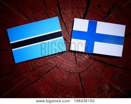 Botswana Flag With Finnish Flag On A Tree Stump Isolated