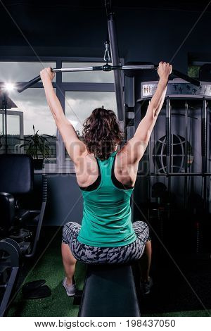 A Back View Of A Trained Girl Doing Exercises. Training For Back Muscles