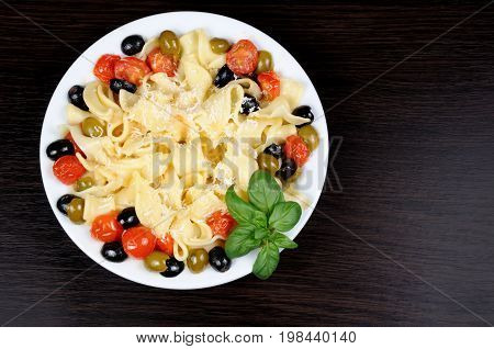 Pasta with olive garlic basil and tomatoes and seasoned with Parmesan cheese. Picture is a top view.
