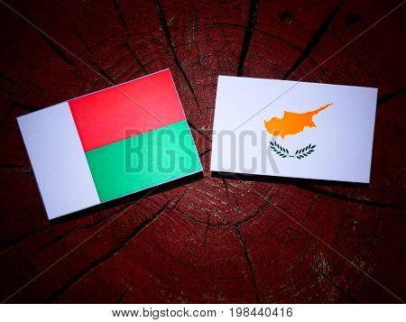 Madagascar Flag With Cypriot Flag On A Tree Stump Isolated