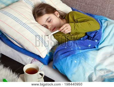A sick child lies in bed with a thermometer