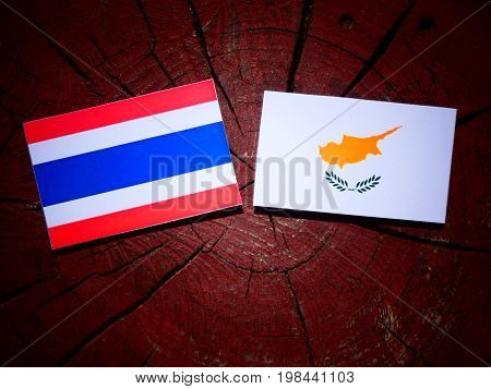 Thai Flag With Cypriot Flag On A Tree Stump Isolated