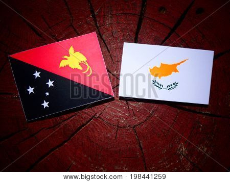 Papua New Guinea Flag With Cypriot Flag On A Tree Stump Isolated