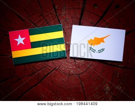 Togolese Flag With Cypriot Flag On A Tree Stump Isolated