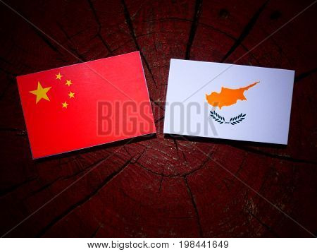 Chinese Flag With Cypriot Flag On A Tree Stump Isolated